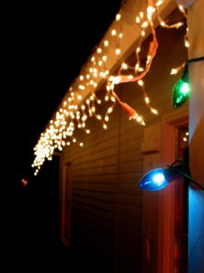 hanging holiday decorations on roof and gutters